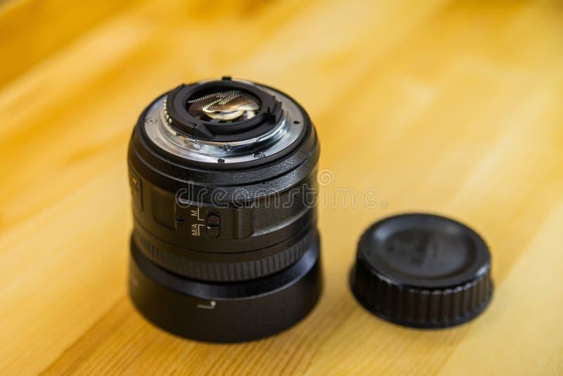Kamera des Foto-DSLR oder Videolinsennahaufnahme auf hölzernem Hintergrund, Ziel, Konzept des Fotografkamera-Mannjobs, nach einem stockbilder