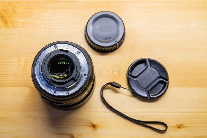 Kamera des Foto-DSLR oder Videolinsennahaufnahme auf hölzernem Hintergrund, Ziel, Konzept des Fotografkamera-Mannjobs, nach einem stockfotos