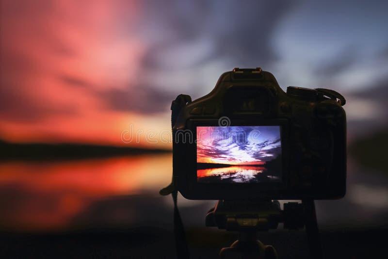 Kamera, die Sonnenuntergang gefangennimmt Fotografieansichtlandschaft lizenzfreie stockfotografie