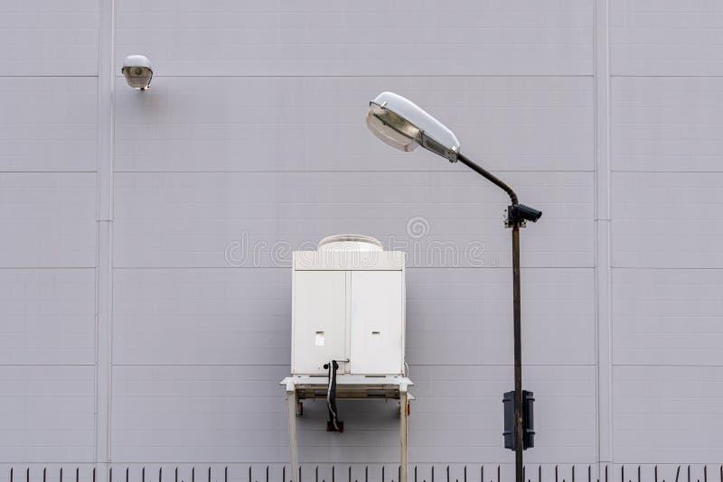 Kamera för gatalampa och bevakning Stor industriell luftkonditioneringsapparat på väggen av en industribyggnad royaltyfria foton