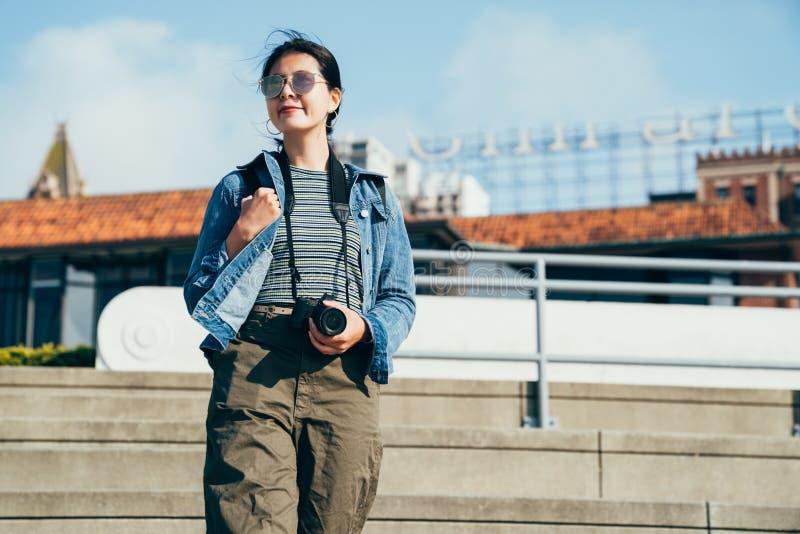 Kamera för innehav för kvinnalinsman som går ner trappa fotografering för bildbyråer