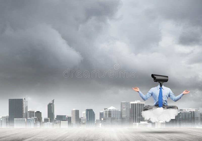 Kamera ging den Mann voran, der in der Lotoshaltung auf Wolke gegen modernes Stadtbild sitzt lizenzfreie stockfotos