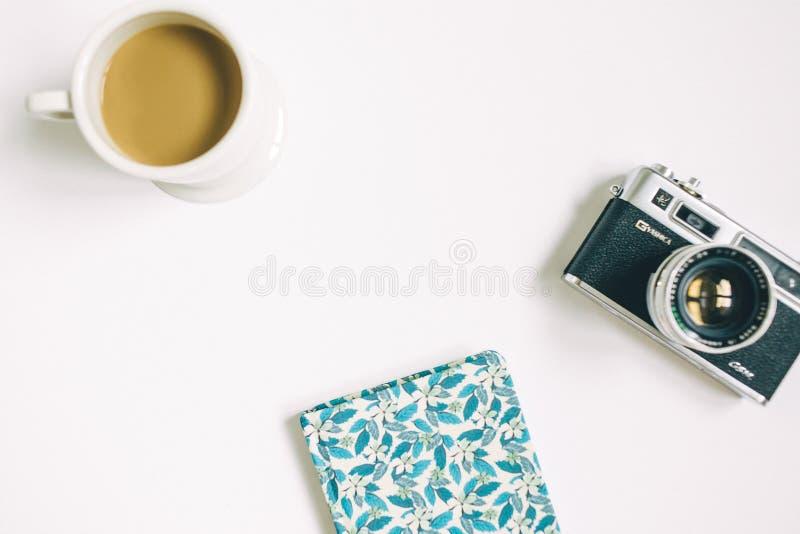 Kamera med notepaden och kaffe