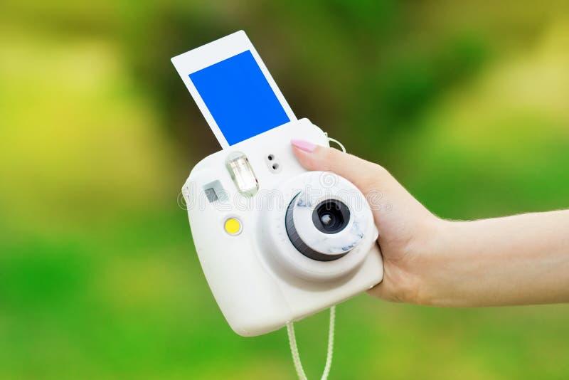 Kamera mit sofortigem Drucken in einer weiblichen Hand auf einem grünen backgro lizenzfreies stockbild