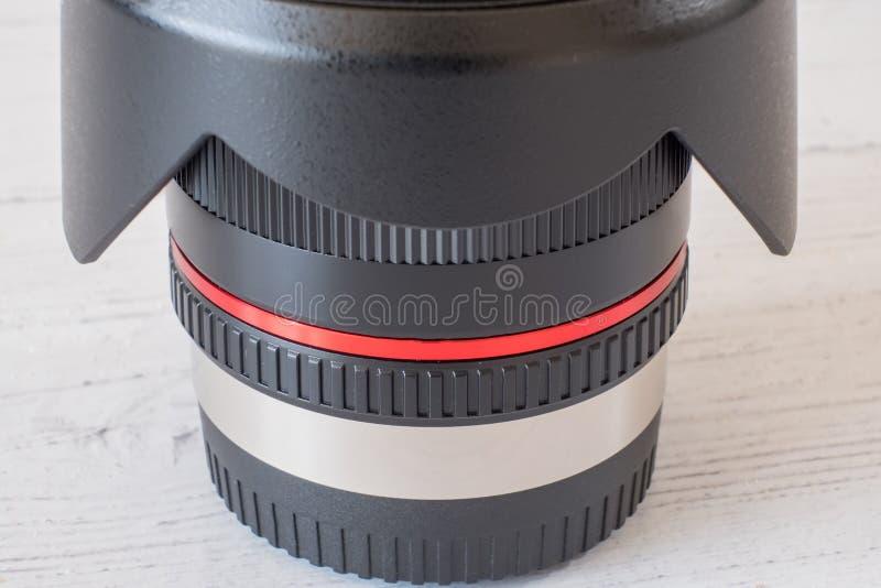Kamera obiektyw na Białej Drewnianej desce z płatka kapiszonem Odwracającym na obiektyw górze fotografia stock
