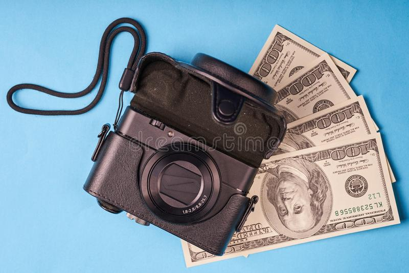 Kamera och en grupp av hundra-dollar amerikanska räkningar fotografering för bildbyråer