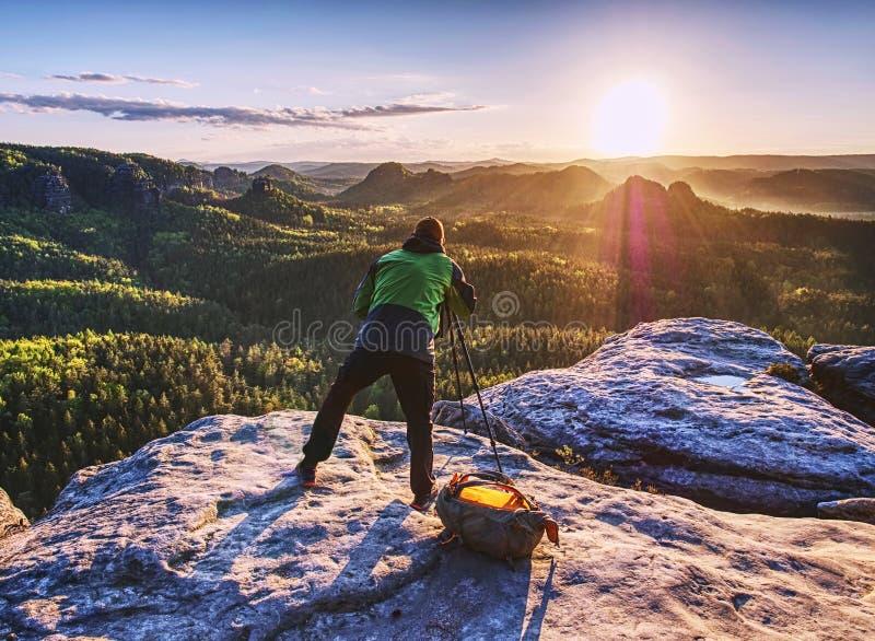 Kamera och tripod för konstnär fastställd som fotograferar soluppgång på toppmöte royaltyfri foto