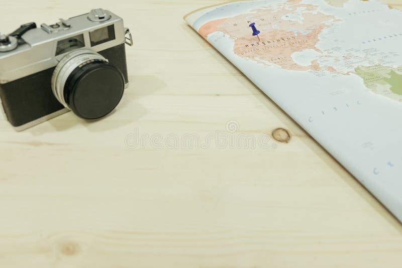 Kamera och världskarta med benpunkt till det Amerika landet båda plommoner royaltyfri foto
