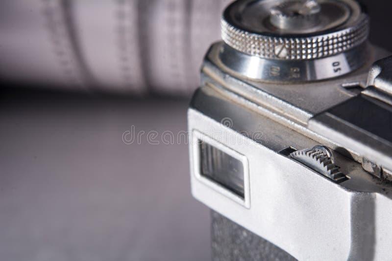 Kamera på bakgrunden av en rulle av den negativa filmen royaltyfria foton