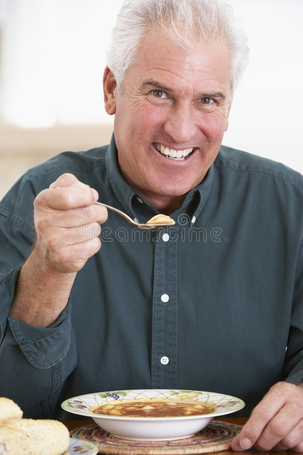 kamera som äter le soup för manpensionär fotografering för bildbyråer