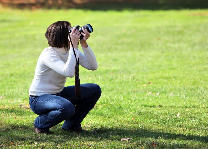 kamera som huka sig ned den nätt kvinnan arkivfoto