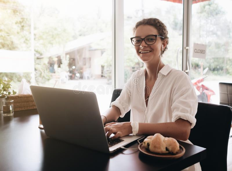 kamera som ser den le kvinnan Student som arbetar på hennes bärbar datordator som sitter i kafé royaltyfria foton