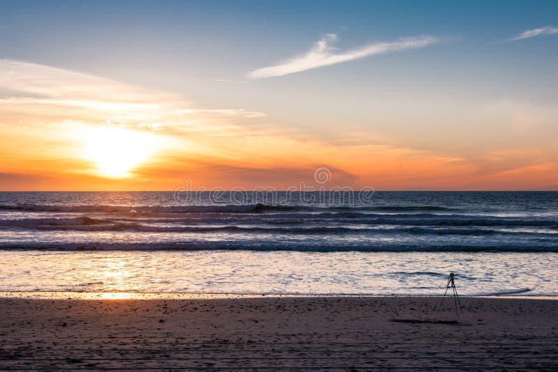 Kamera z tripod mknącym zmierzchem przy plażą z pięknym zmierzchem obrazy stock