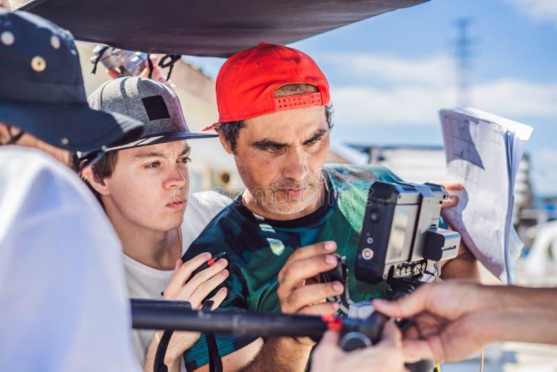 Kamerabetreiber, -direktor und -dP besprechen den Prozess eines Handelsvideodrehs lizenzfreies stockfoto