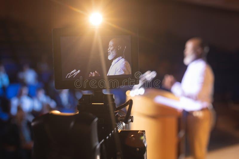 Kamerainspelningaffärsman som ger anförande i salong royaltyfri fotografi