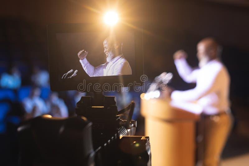 Kamerainspelningaffärsman som ger anförande i salong fotografering för bildbyråer