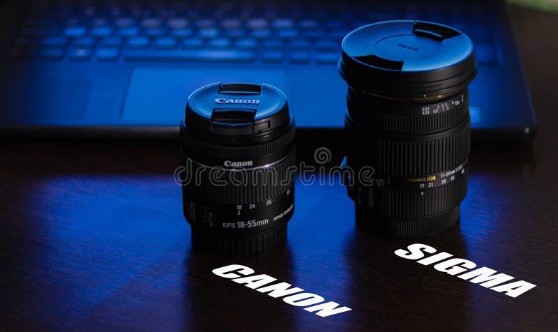 Kameralinser Canon och sigma på tabellen med blått violett ljus från bakgrunden, bärbar datortangentbord- och handlagblocket och  royaltyfri bild