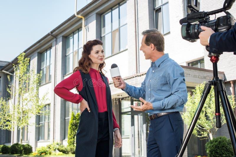 kameraman och manlig nyheternareporter som intervjuar den lyckade affärskvinnan royaltyfria foton