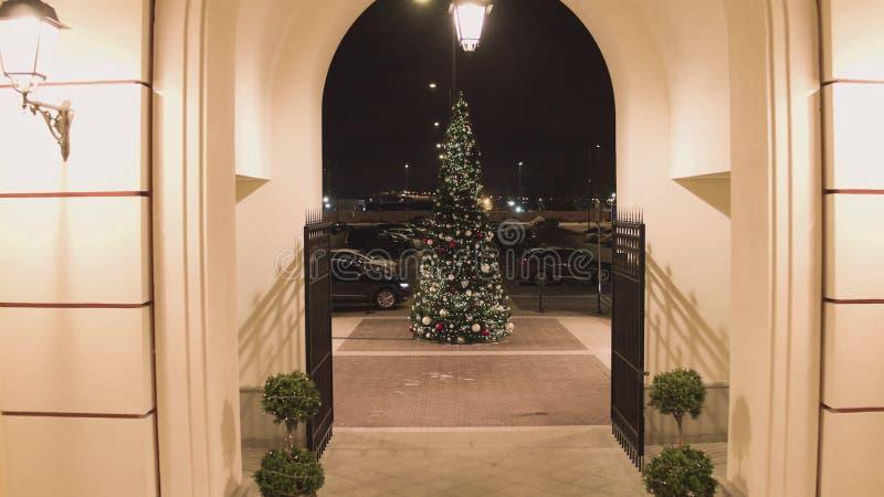 Kameran kommer ut ur byggnad och får närmare dekorerat sörja-träd royaltyfri fotografi
