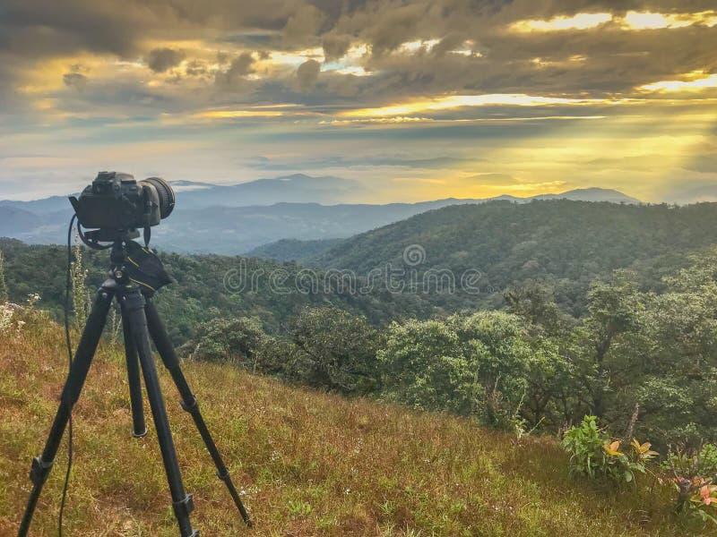 Kameran och ställningen tar tidschackningsperiod överst av berget och den ljusa strålen royaltyfri bild