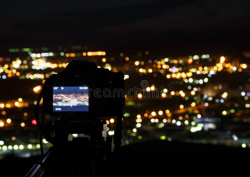 Kameran på bakgrunden av staden på natten arkivbild