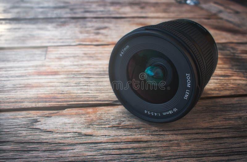 Kameraobjektiv auf einem rustikalen Holztisch lizenzfreie stockfotos