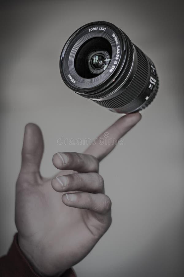 Kameraobjektiv, das auf einem Vinger frei schwebt stockbild