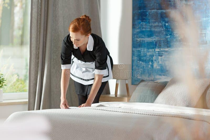 Kamermeisje schoonmakend beddegoed stock afbeeldingen
