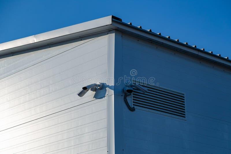 Kameror av video bevakning på hörnet av byggnaden mot den blåa himlen arkivfoton