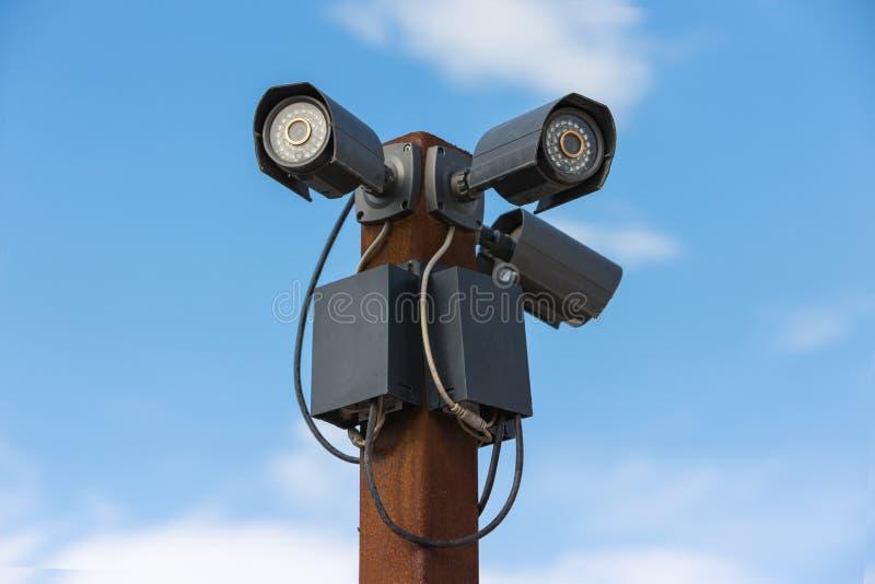 Kameror för CCTV-säkerhet tre mot på himlen royaltyfri foto