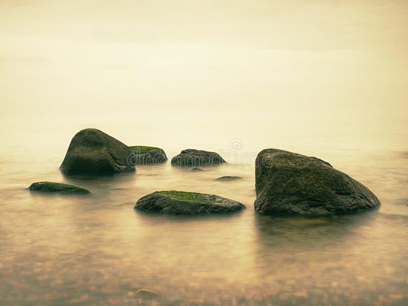 Kamieniści brzegowi igrania ocean rozjaśniają niebo z zamazanym słońcem w wysokiej wilgotności obraz stock