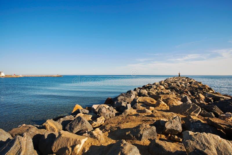 Kamieni falochrony ochraniać nabrzeżne struktury od niszczycielskiego wpływu burzy morze machają Cabopino plaża obraz royalty free