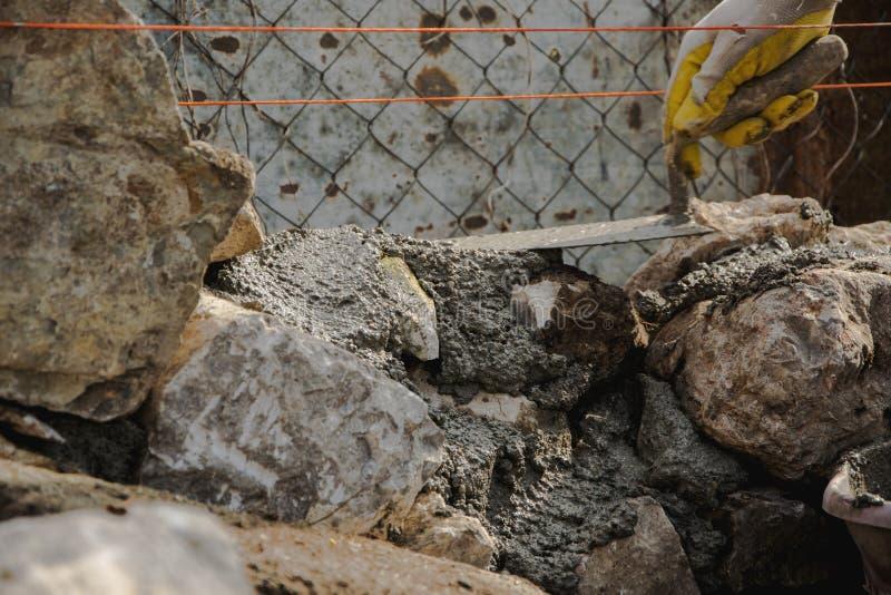 Kamieniarz buduje kamienną ścianę, autentyczna pracująca osoba zdjęcie stock
