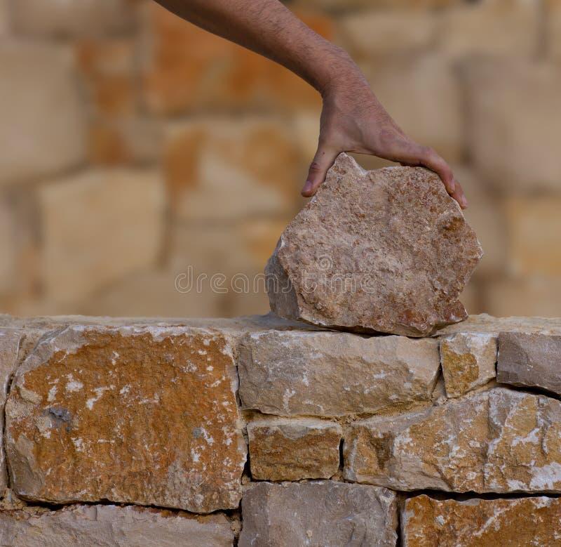 Kamieniarz wręcza działanie na kamieniarstwo kamiennej ścianie zdjęcie stock