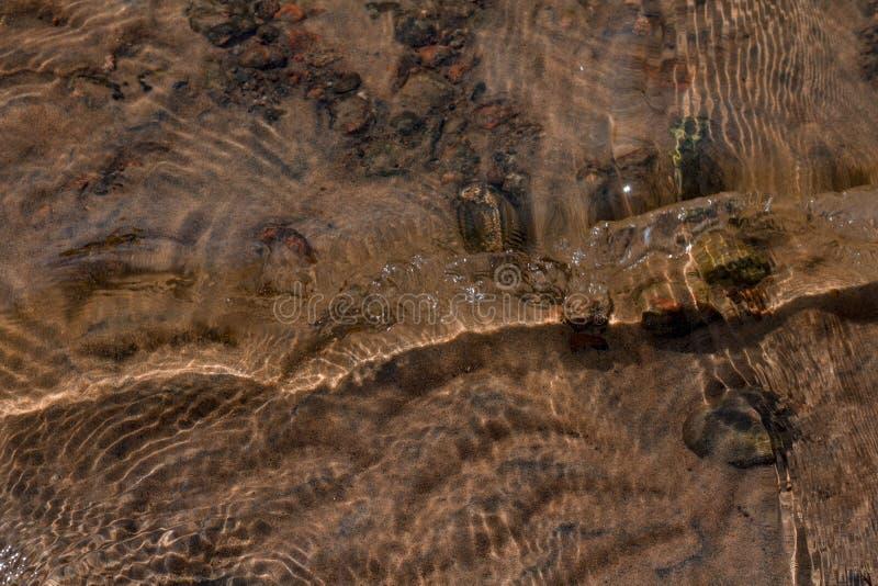 Kamienie pod wod? z falami w przedpolu i piasek zdjęcie royalty free