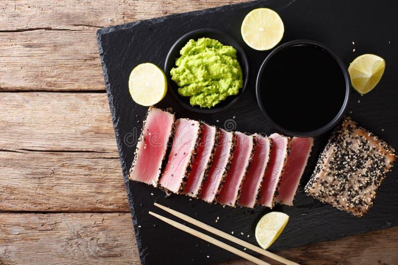 Kamienna łupkowa taca z pokrojonym tuńczyka stkiem smażył w sezamowych ziarnach T fotografia royalty free