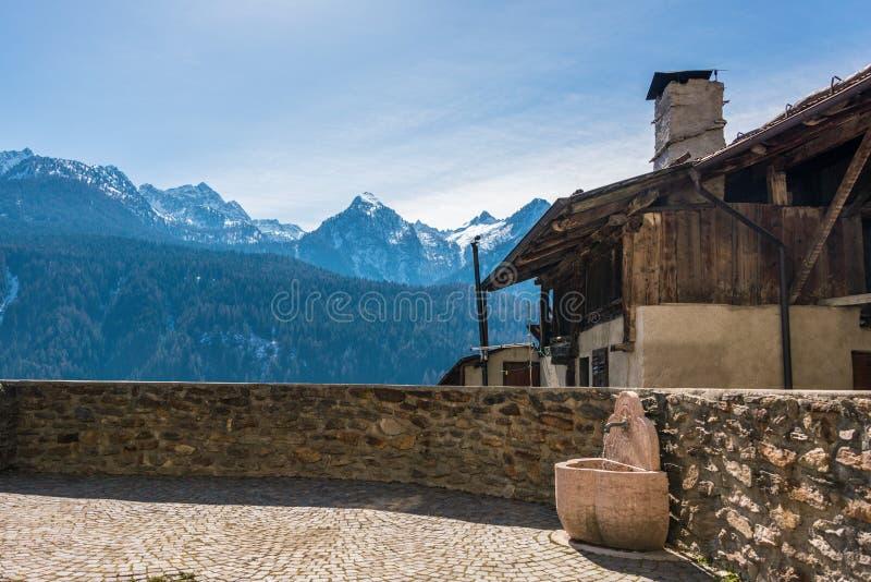 Kamienna ściana i fontanna z wodą pitną i starym włoszczyzna domem budującymi, drewno i kamienie z śniegiem zakrywaliśmy góry zdjęcie royalty free