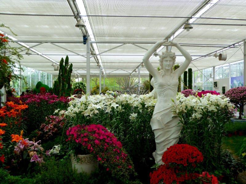Kamienna kobiety statua z kwiatami otaczającymi fotografia stock
