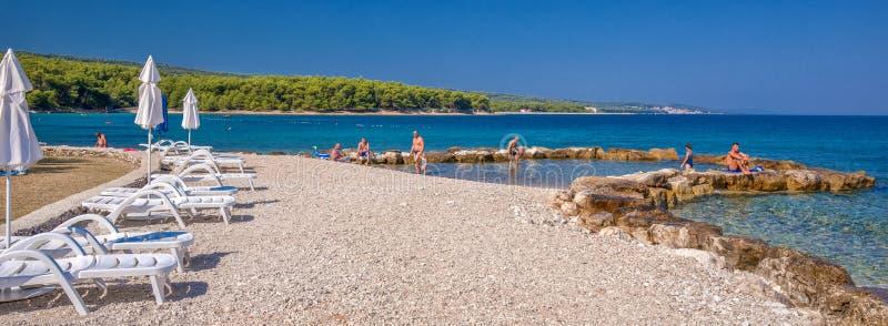 Kamienna plaża na Brac wyspie z turkusu jasnego oceanu wodą, Supetar, Brac, Chorwacja zdjęcia royalty free