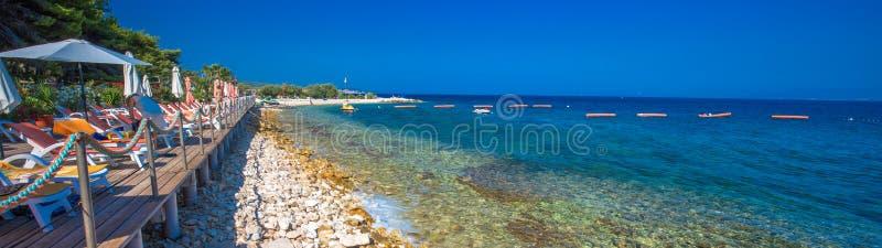 Kamienna plaża na Brac wyspie z turkusu jasnego oceanu wodą, Supetar, Brac, Chorwacja obrazy stock