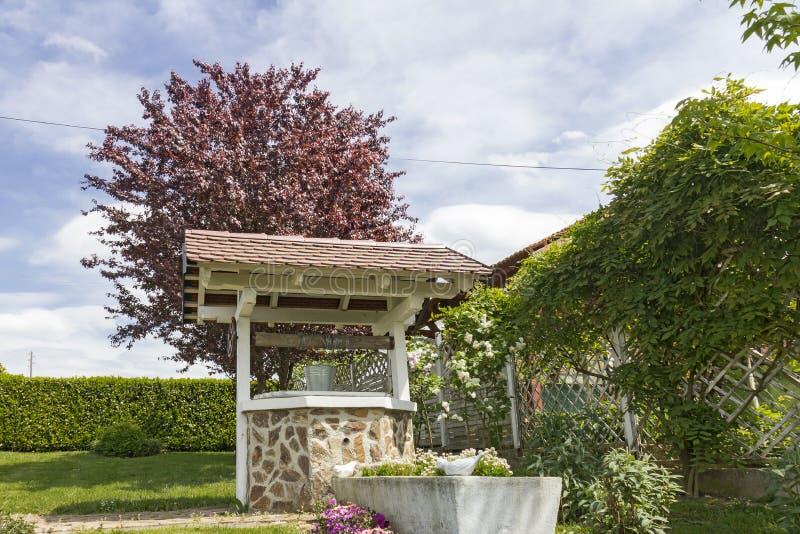 Kamienna wodnego well pozycja przed czerwonym śliwkowym drzewem obrazy stock
