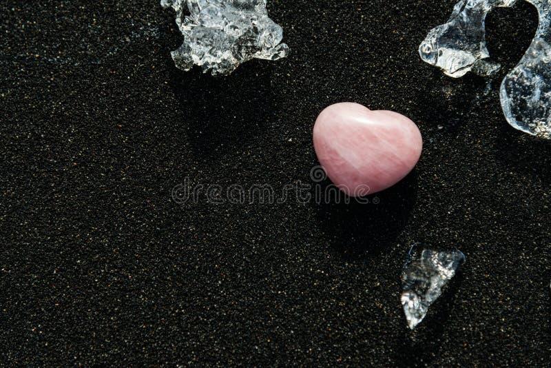 Kamienni serca i lodu kawałki na czarnym piasku fotografia royalty free