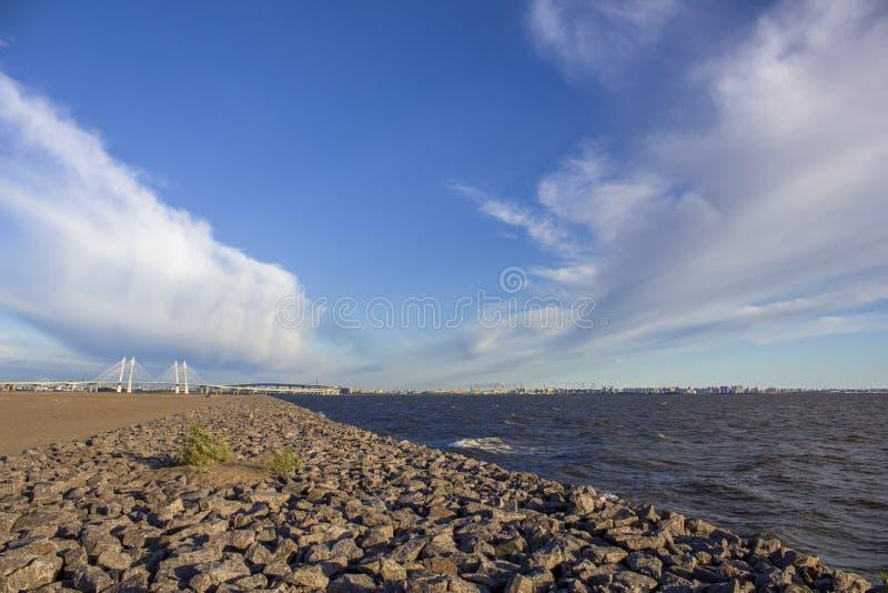 Kamienny denny deptak w piaskowatej pustyni przeciw białemu zostającemu mostowi i nowożytnym mieście pod ciężkim niebieskim niebe zdjęcie stock