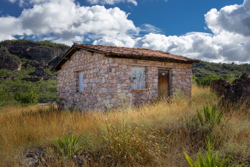 Kamienny dom na wsi w polu z chmurnym niebem jako tło i wzgórzem fotografia royalty free