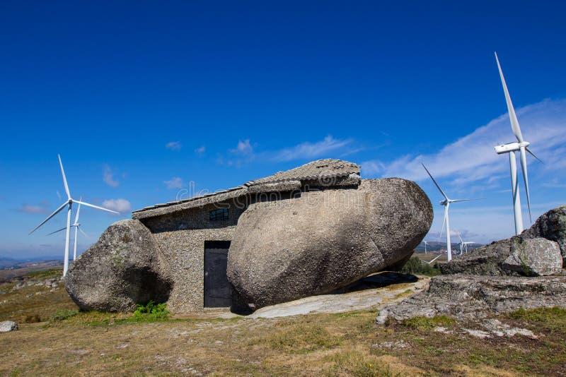 Kamienny dom, silnik wiatrowy, niebieskie niebo zdjęcia royalty free