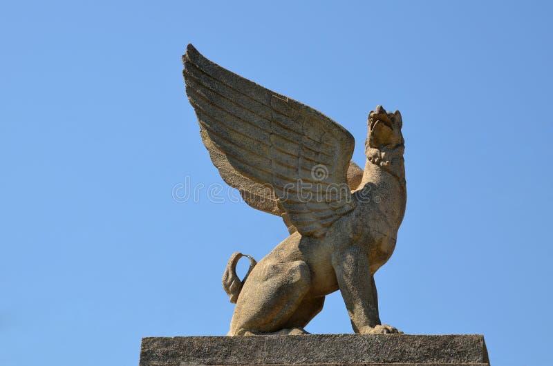 Kamienny gryf siedzi na piedestale przeciw niebieskiemu niebu w obraz royalty free