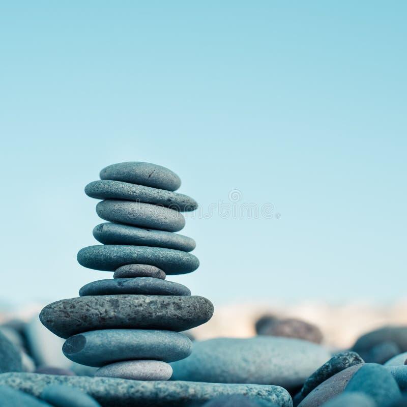 Kamienny kopiec na zielonym rozmytym tle, otoczakach i kamieniach, Pojęcie równowaga fotografia stock