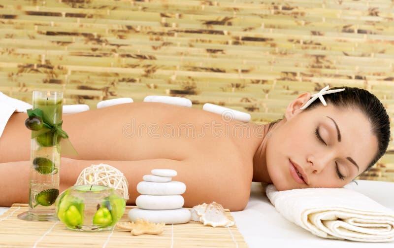 Kamienny masaż dla kobiety przy zdroju salonem. fotografia royalty free