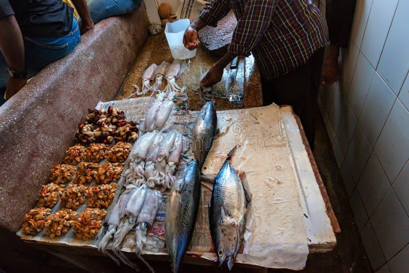 KAMIENNY miasteczko ZANZIBAR, STYCZEŃ, - 9, 2015: Ludzie sprzedają dennego jedzenie w rybim rynku obraz stock