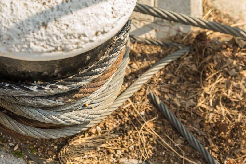 Kamienny piedestał coiled żelaznego kablowego cumowania fiksacja potężnego statek na piaska tle w górę kopii przestrzeni obraz royalty free